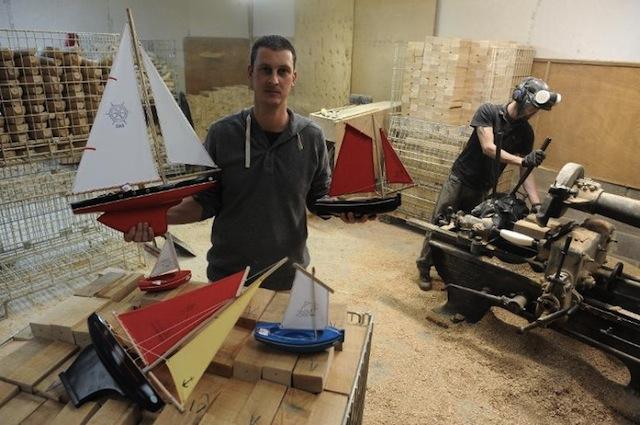 fabricant tirot pose avec des jouets bateaux en bois a cote d'un employ